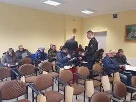 W trosce o bezpieczeństwo_3 zdjęcie przedstawia: siedzących ludzi na sali a przy nich dwóch mężczyzn rozdających kartki
