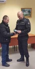 W trosce o bezpieczeństwo_4 zdjęcie przedstawia: strażaka przekazującemu mężczyżnie małe urządzenie