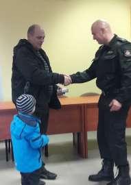 W trosce o bezpieczeństwo_6 zdjęcie przedstawia: strażaka podającego dłoń w uścisku w kierunku mężczyzny obok stoi dziecko