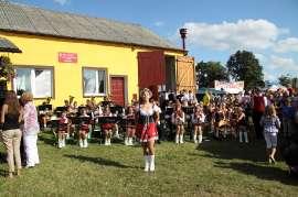 Dożynki Gminne Święcia 2011: Zdjęcie przedstawia mażoretkę oraz orkiestrę w tle