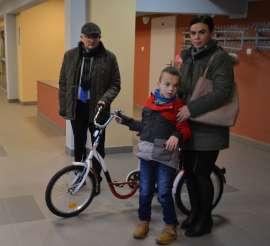 Przekazanie Rowerów Eco Textil_3 zdjęcie przedstawia: dwie dorosłe osoby i dziecko stojące przy rowerze