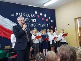 zdjęcie przedstawia:mężczyznę z mikrofonem w tle stojące dzieci