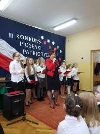 Konkurs piosenki w Grochowach_2:zdjęcie przedstawia: kobietę a za nią stojące dzieci