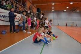 Olimpiada: Zdjecie przedstawia siedzące dzieci na podłodze hali sportowej