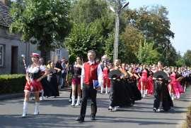 Przedszkolaki_1: Zdjęcie przedstawia grupę osób maszerujących przez ulicę. Ubrani są w biało-czerwono-czarne stroje.