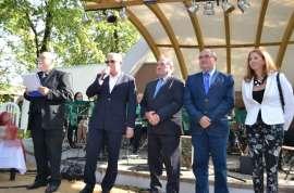Przedszkolaki_3: Zdjęcie przedstawia jedną panią w białym żakiecie i czterech panów w ciemnych garniturach.