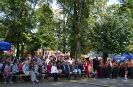 Przedszkolaki_5: Zdjęcie przedstawia ludzi siedzących na ławkach i stojących pod drzewem.