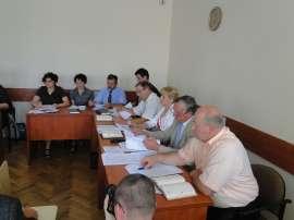 Sesja absolutoryjna_3: Zdjęcie przedstawia kobiety i mężczyzn siedzących przy złączonych biurkach.