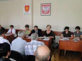 Sesja absolutoryjna: Zdjęcie przedstawia siedzących ludzi i dwa obrazki na ścianie.