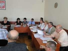 Sesja absolutoryjna_6: Zdjęcie przedstawia panie i panów siedzących przy biurkach.