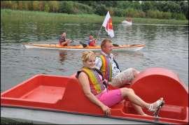 Wilczyn Ruszenie Powiatu: Zdjęcie przedstawia ludzi na kajaku i rowerku wodnym płynących po jeziorze.
