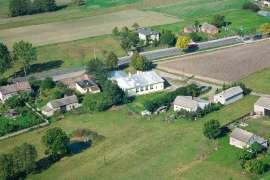 Z lotu ptaka: Zdjęcia przedstawia drogę, pola uprawne i zabudowania widziane z wysokości.
