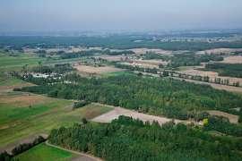 Z lotu ptaka: Zdjęcia przedstawia lasy, pola i zabudowania widziane z wysokości.